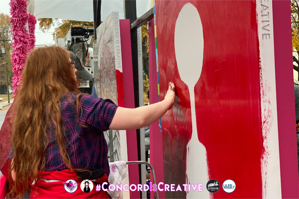 Artist smearing red paint onto her large metal canvas