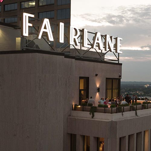 Dusk atop Fairlane Luxury Hotel building with bright neon sign on top of roof in Nashville TN