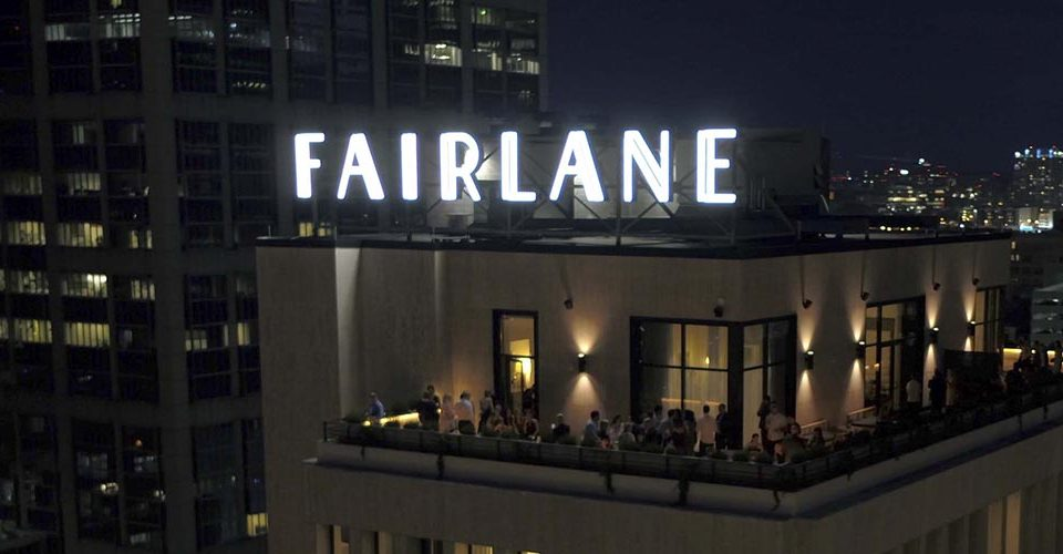 People at Fairlane rooftop bar with bright neon sign atop the building