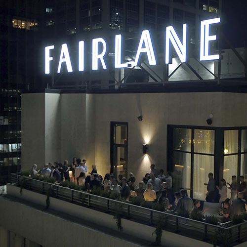 Rooftop Fairlane Luxury Hotel sign at night above people at bar