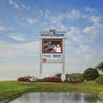 Inlet square shopping center sign with watchfire emc in front of pond
