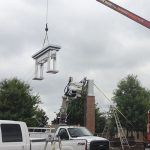 Rite Lite crane installing cap of shopping center pylon sign