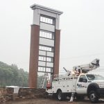 Rite Lite boom truck installing faces to shopping center pylon sign