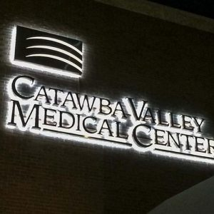 Halo lit brushed metal trimless channel letters entrance wall sign to hospital
