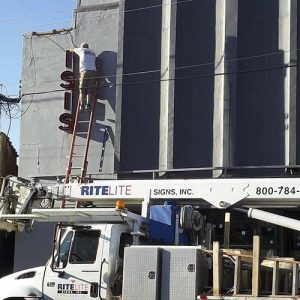 Technician installing Isis neon channel letters to building in Asheville, NC
