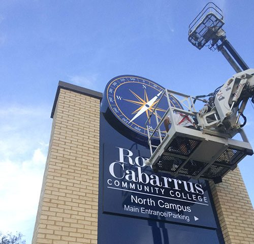 Rite Lite boom truck installing Rowan Cabarrus Community college pylon sign