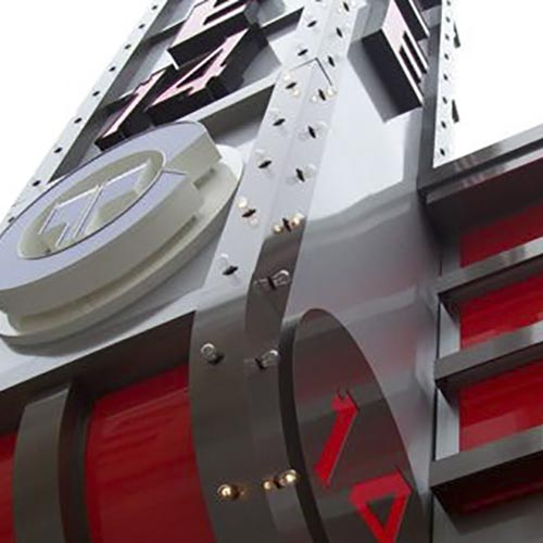 Installation of large custom fabricated cinema blade sign during the day