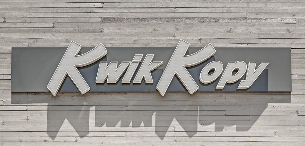 Textured Chanel letters installed on wall sign for Kwik Kopy retail business
