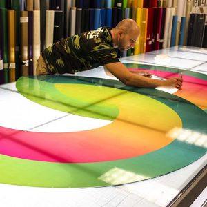 Rite Lite technician carefully cutting McCullough printed vinyl logo