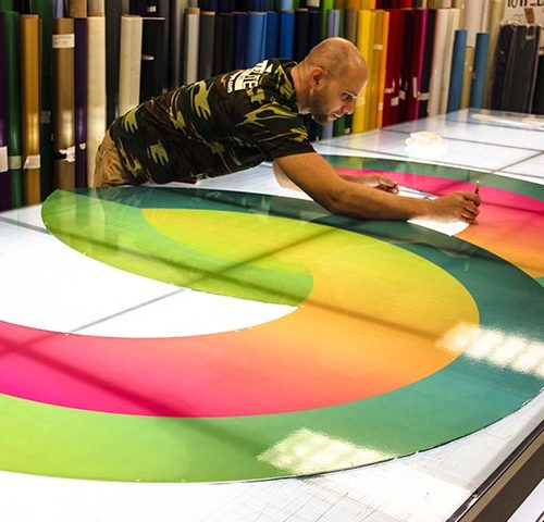 Rite Lite technician carefully cutting McCullough printed vinyl logo