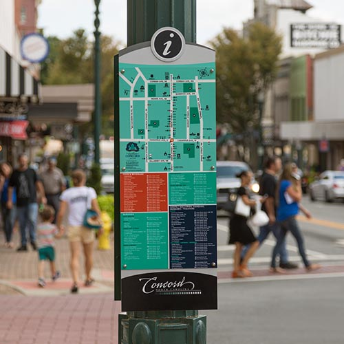 Digitally printed vinyl graphic on pole sign with people walking around downtown Concord, NC