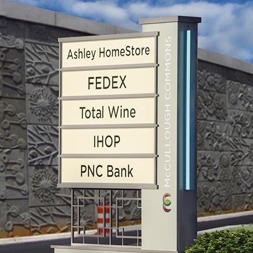 Custom shopping center entrance pylon tenant panel sign in front of Light Rail in Charlotte NC