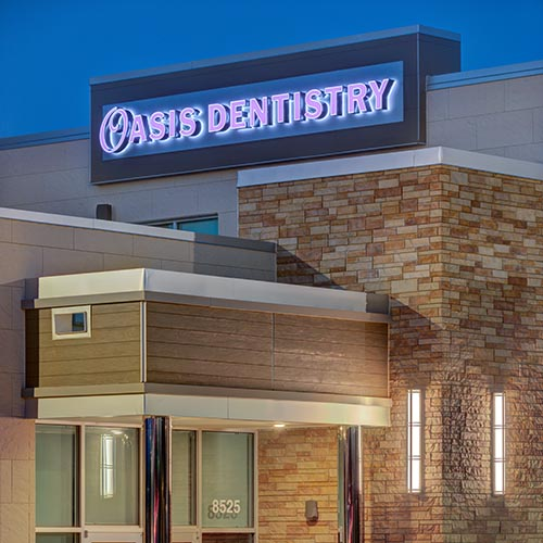 Custom healthcare wall signage with halo illumination and purple channel letters on building