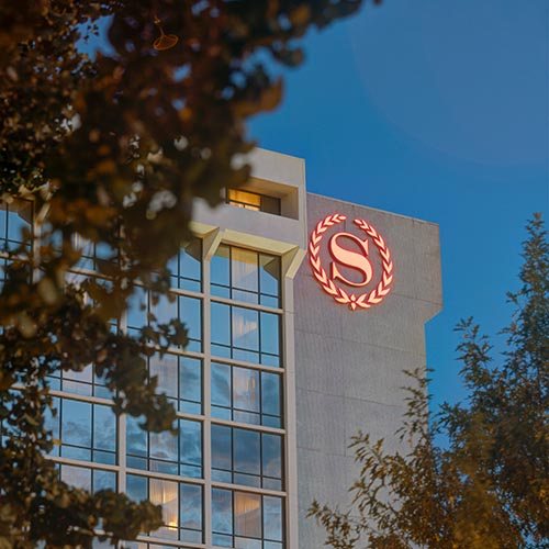 Red Sheraton logo wall sign installed on the top of the Charlotte hotel