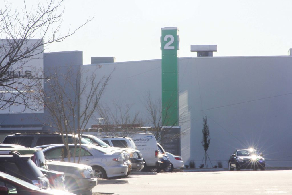 Large green steel structure with glass panels in parking lot of concord mills mall