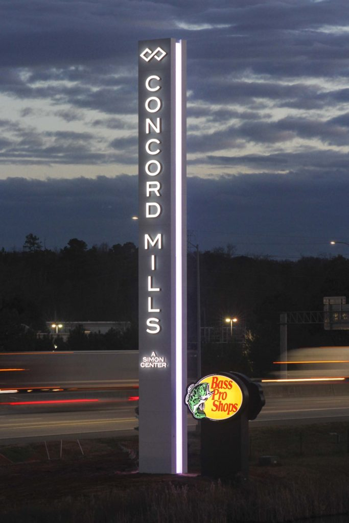 70' steel concord mills mall sign illuminated in front of a blurry highway at night