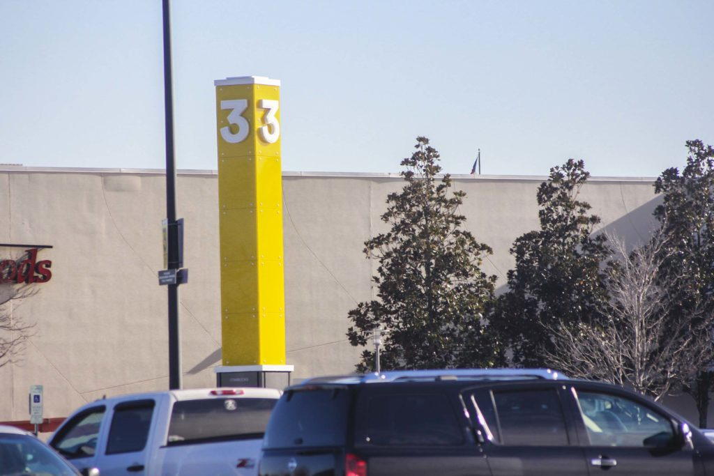 Large yellow steel structure with glass panels in parking lot of concord mills mall