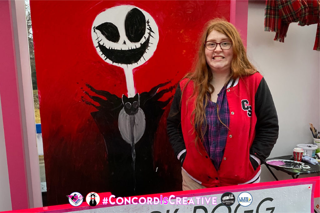 Happy artist poses with mural of skeleton figure on red background on a large metal canvas