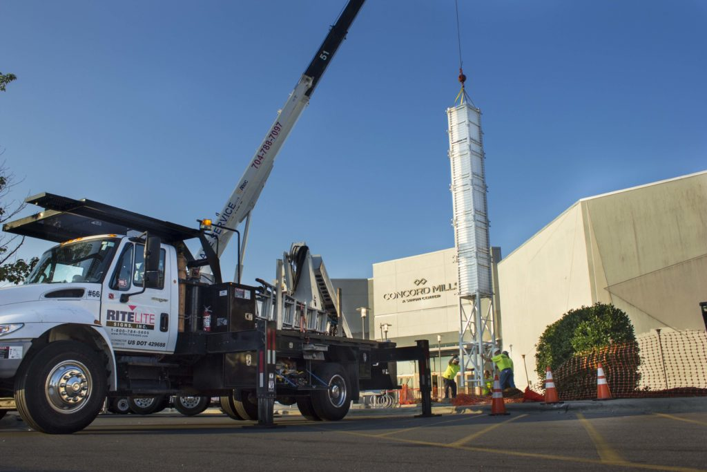 Rite Lite crane truck hoisting up a large metal structure for concord mills mall