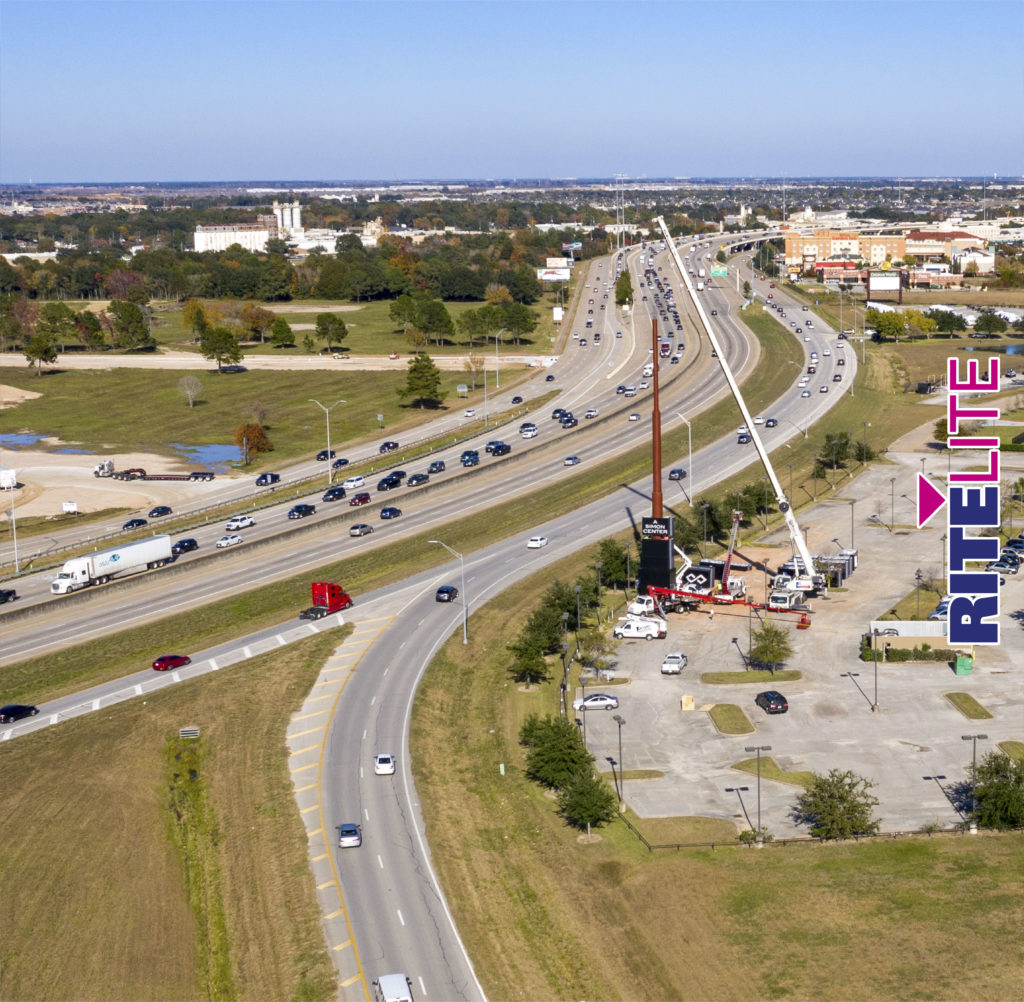 Aerial view of cars on highway and crane truck installing Katy Mills pylon sign