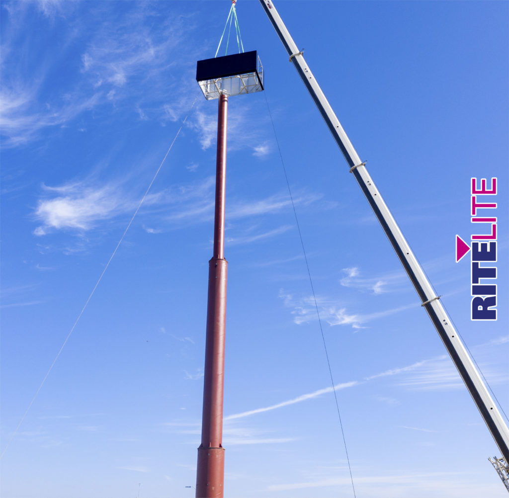 Crane arm holding section of metal pylon sign above the telescoped pole