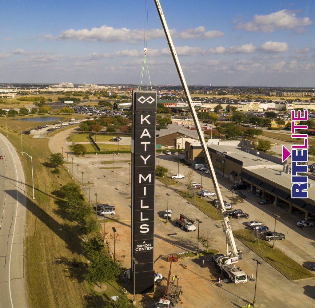 A large crane installing the final section in the Katy Mill Mall Sign