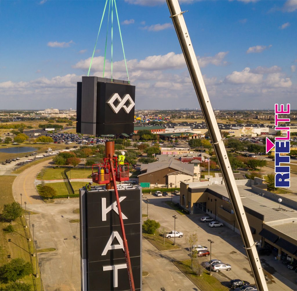 Top section hanging from crane about to be placed on top of 120' pylon sign