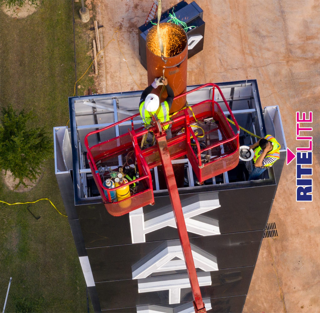 Overhead view of technician cutting steel pole on Katy Mills sign