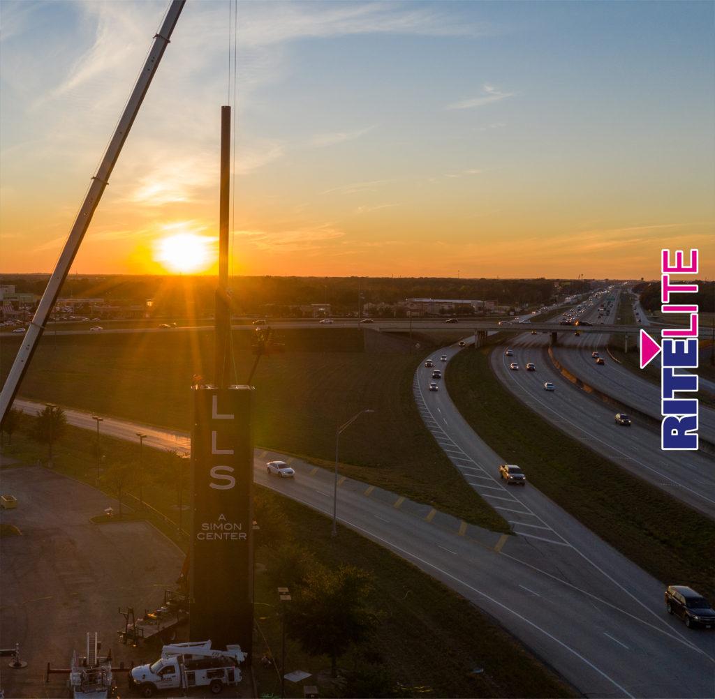 Sun setting behind a half assembled Katy Mills pylon sign