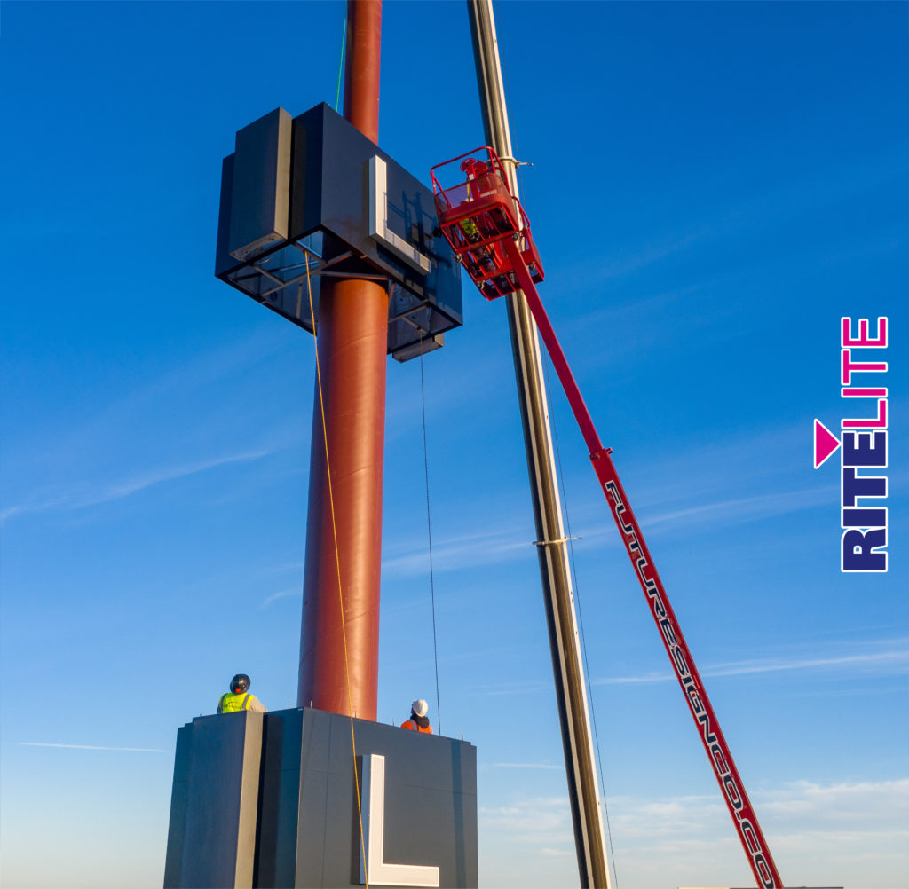 Cranes assist a section of the large pylon sign