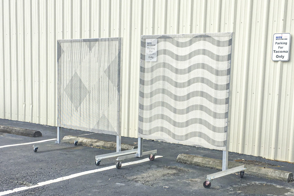 Etched stainless steel gkd metal fabric samples in daytime parking lot at Rite Lite Signs