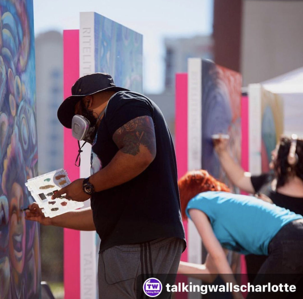 John Hairston and Sharon Dowell paint metal canvases at 2018 Talking Walls mural festival